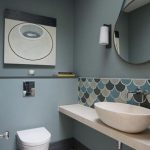 Bathroom, Patterned Floor Tiles, Green Wall, Patterned Backsplash, White Floating Shelf, White Sink, Round Mirror, White Toilet