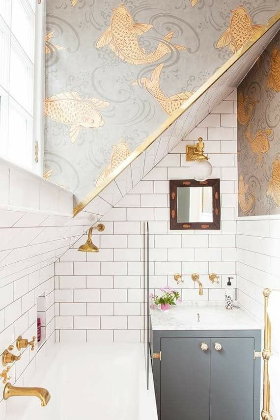bathroom, whit tub, white squre wall tiles, grey wallpaper with golden fish, golden faucet, sconces, and rails