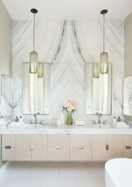 bathroom, white floor tiles, long wooden cabinet, white marble wall, mirrors, beige wall, glass pendants