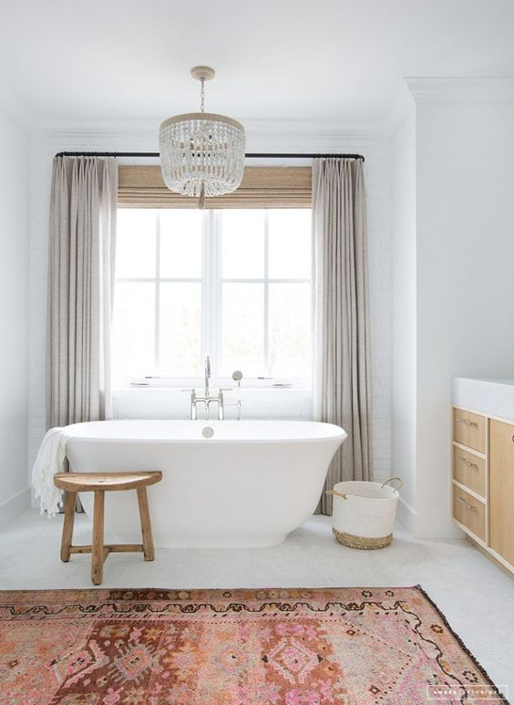 bathroom, white floor, white wall, beige curtain, white tub, red rug, wooden stool, wooden cabinet with white top, chandelier