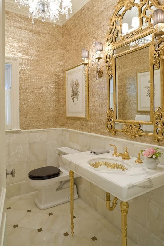bathroom, white gold floor tiles, golden mosaic wall, white marble wainscoting, golden framed mirror, white sink with golden faucet and golden legs, chandelier