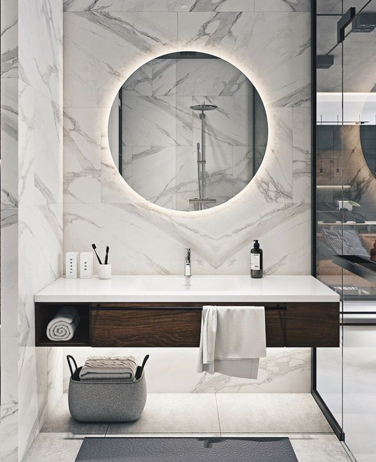 bathroom, white marble floor, white marble wall, round mirror with LED light on the back, floating vanity with white top