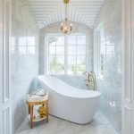 Bathroom, White Marble Ont He Floor, Wall, Patterned Ceiling, Chandelier, White Tub, Golden Faucet, Wooden Stol