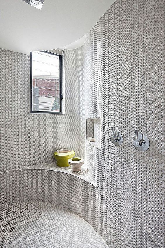 bathroom, white tiny hexagonal tiles on the entire wall and floor, dented shelves, dented alcove