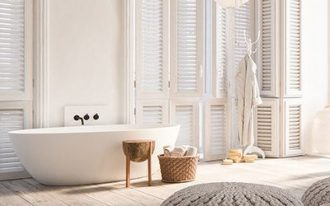 bathroom, wooden floor, rattan ottoman, white tub, white wall, high arch window, white lantern, wooden stool and basket