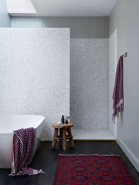 bathroom, wooden floor, white tub, grey wall, tiny mosaic tiles on the wall, floor, partition, rug, wooden stool