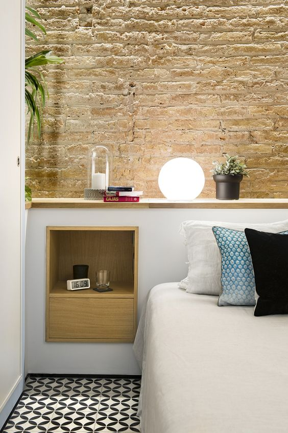 bedroom, patterned tiles, white headboard, wooden layered shelves, wooden square shelves and drawer, open brick wall, white bedding