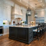 Big Kitchen Islands Glass Pendant Lamps Black Island Black Barstools Granite Countertop Wooden Floor White Cabinet Built In Appliances Stovetop Sink