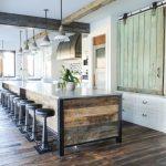 Big Kitchen Islands Reclaimed Wood Island White Countertop Black Barstools Wooden Floor White Cabinets Pendant Lamps Wine Fridge Sink Stovetop Shelves