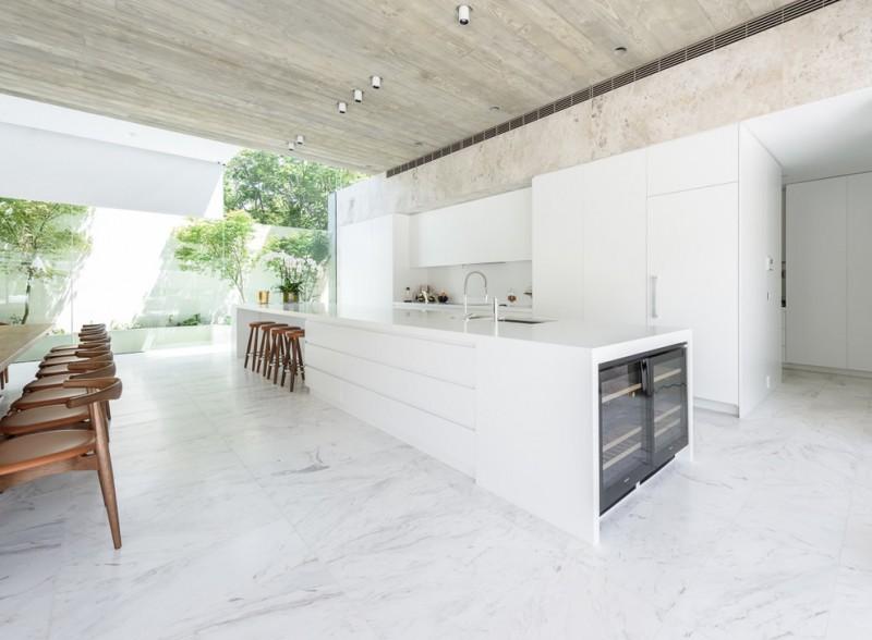 big kitchen islands white island white flat panel cabinets white backsplash white countertops wooden stools wine fridge stovetop white marble floor tile sink
