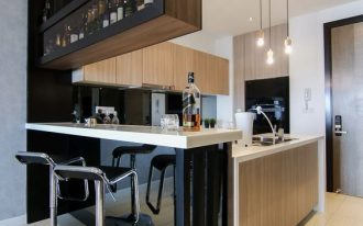 black bar with whtie top added to wooden look kitchen with pendants, black steel stool