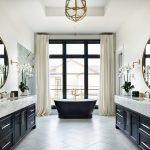 Black Bathroom Cabinets Glass Chandelier Black Freestanding Tub Glass Doors Beige Curtains Large Round Wall Mirrors Wall Sconces White Marble Top Sink Faucet