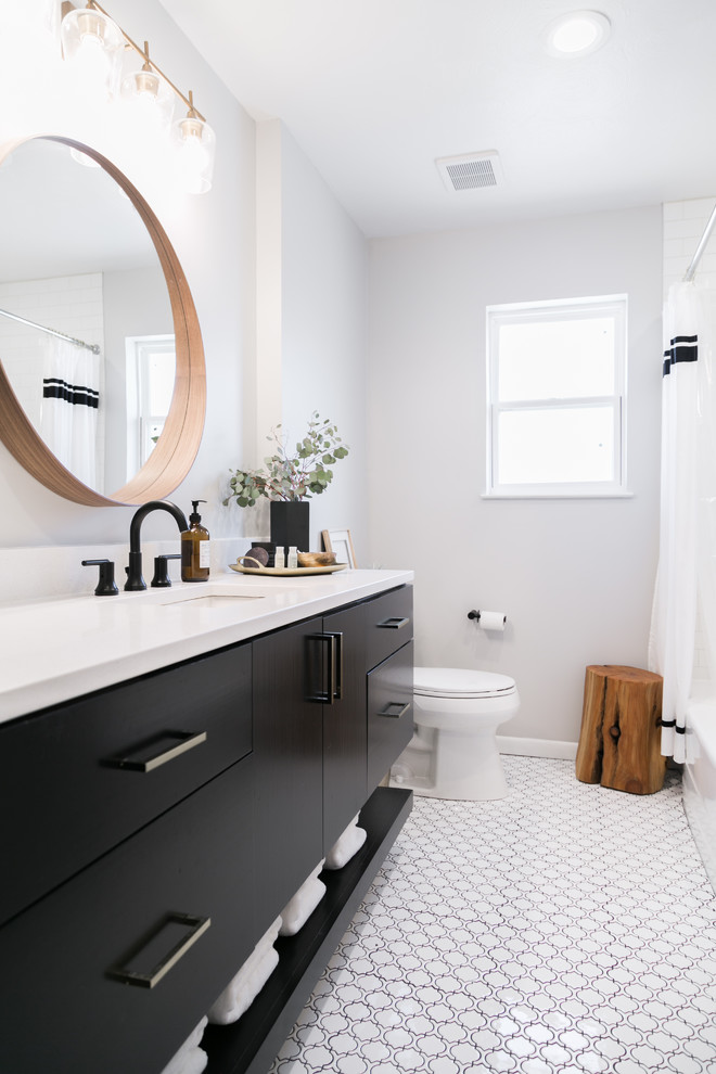 black bathroom cabinets round wall mirror white countertop white sink black faucet window white curtains wooden stool toilet white mosaic floor tile window shade