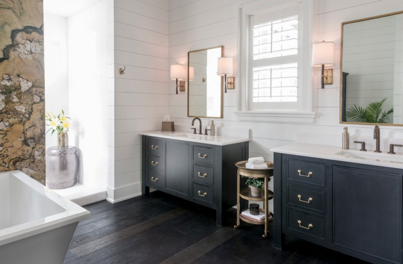 black bathroom cabinets wall sconces wall mirror window round cart wooden floor towel hook white walls acrylic bathtub