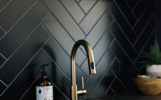 black herringbone backsplash tiles, wooden floating shelves, black top, black cabinet with golden handler