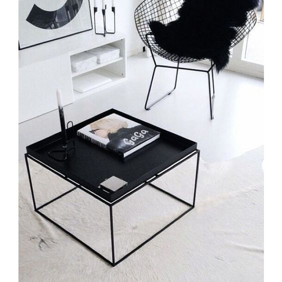 black tray coffee table, white floor, white rug, black wired lounge chair, white shelves