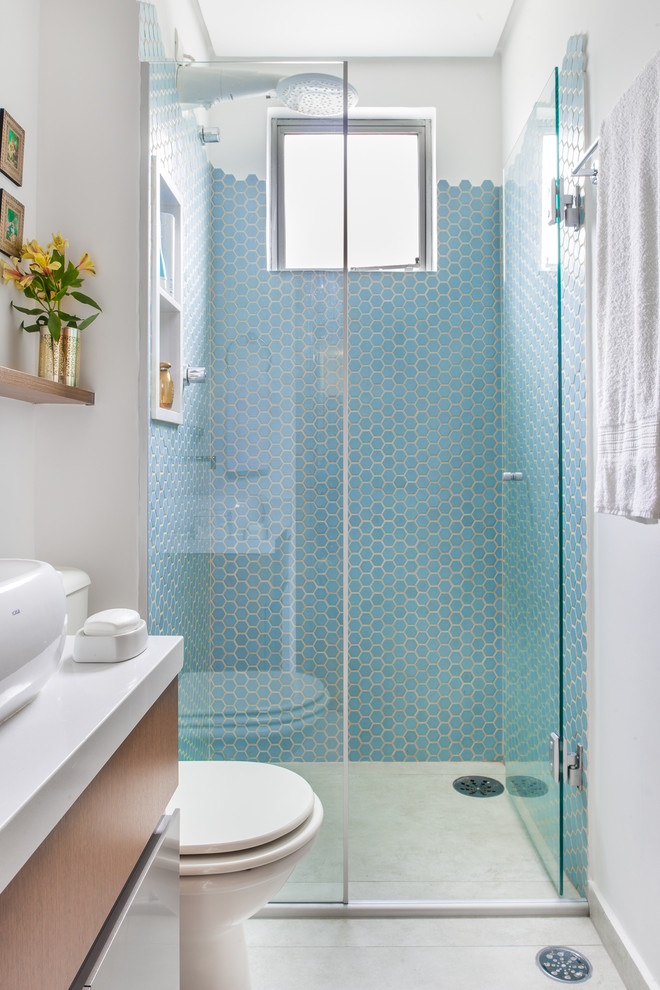 blue wall tile hexagonal tile built in shelves window glass shower door vanity white sink bowl wall mounted shelf toilet white rainfall shower head towel holder