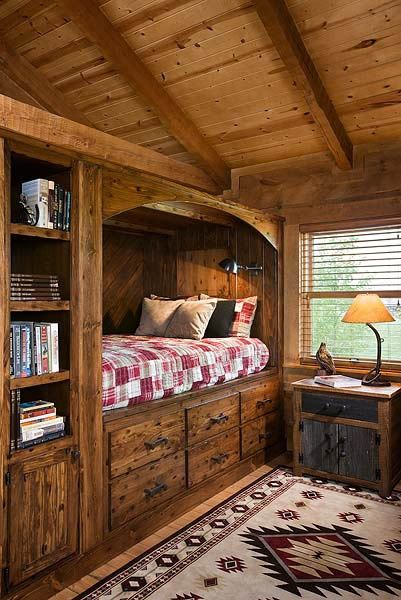 cabin home, wooden ceiling, wooden bed with drawers under, shelves, wooden floor, wooden side cabinet