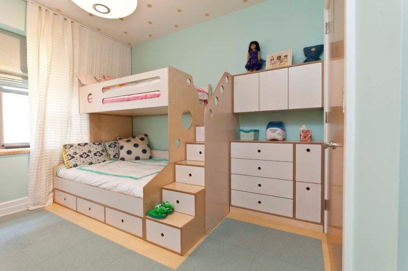 custom kids bed pendant lamp bunk bed white drawers white built in dresser white curtains glass windows white bedding blue wall pillows staircase with drawers