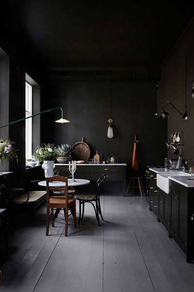 dark kitchen, grey floor, black bottom cabinet with white countertop, white sink, dark brown cabinet, black pendant, white dining table, dark chairs