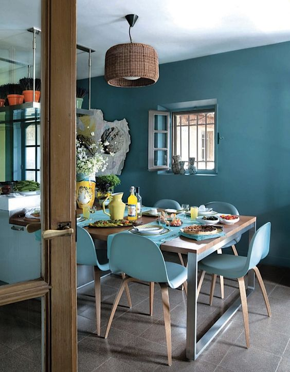 dining room, beige floor, blue wall, blue chairs, wooden table, rattan covered pendant, plants on hanging shelves