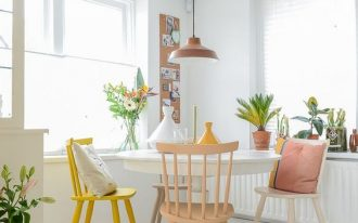 dining room, white wooden floor, white wooden round table, pink, peach, white, yellow chairs, brown pendant, whtie wall and ceiling
