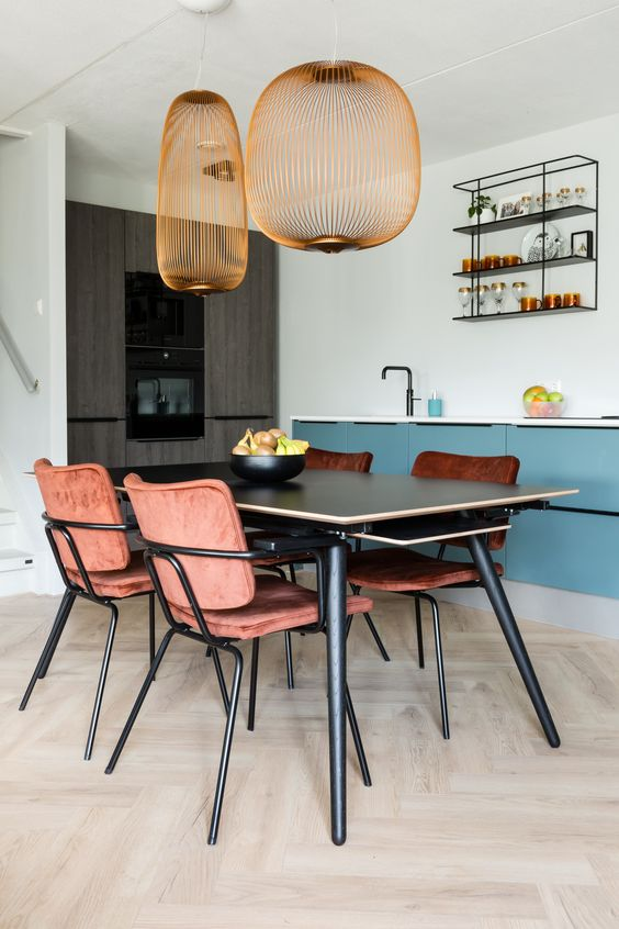 dining room, wooden floor, black wooden table, warm terracotta chairs, golden wired pendants, blue cabinet, white wall, wire floating shelves, grey cabinet