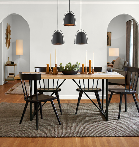 dining room, wooden floor, grey rug, black wooden chairs, light wooden table, black pendant, arch
