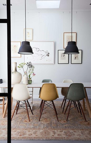 dining table with white table, white yellow green midcentury modern chairs, white wall, black pendants, soft rug, grey floor