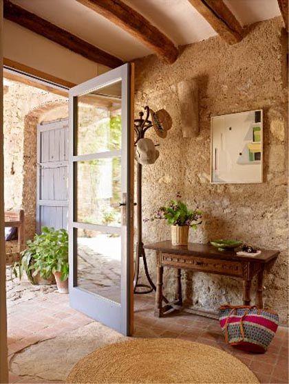 entrance, earthy floor tiles, rattan rug, earthy brown textured wall, wooden table, hat rack, glass door