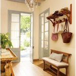 Entrance, Wooden Floor, Beige Wall, Wooden Bench With White Cushion, Wooden Table, Rattan Basket, Wooden Floatng Shelves, Chandelier, Grey Wooden Beams