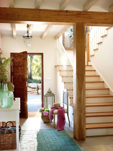 entrance, wooden floor, wooden beam posts on the ceiling and stairs, white wooden table, rattan basket, white chair, glass pendant, wooden door