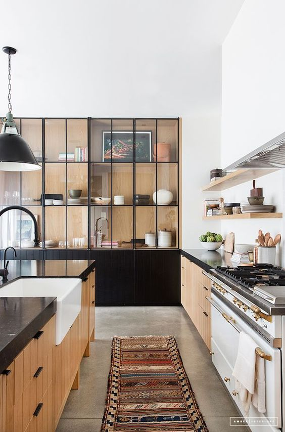 galley kitchen, grey seamless floor, wooden bottom cabinet with black top, black built in cupboard with glass door, black pendant, wooden floating shelves