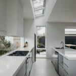 Galley Kitchen, White Seamless Floor, White Wall, White Ceiling, Clear Glass Ceiling, Clear Glass Backsplash, Grey Bottom Cabinet, Shelves