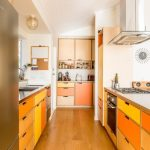 Galley Kitchen, Wooden Floor, White Wall, Yellow Orange Brown Cabinet Blocks, Steel Ktchen Top, Pendant, Steel Hood