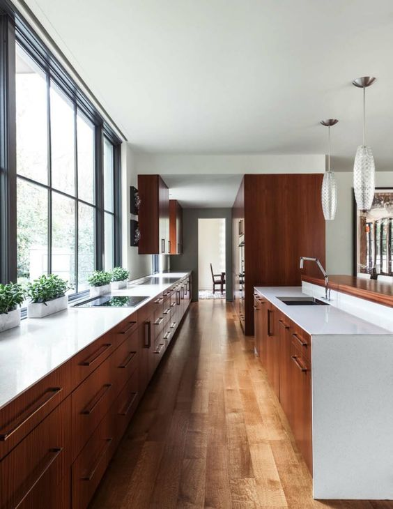 galley kitchen, wooden floor, wooden bottom cabinet, white top, glass wall, white wall ceiling, long glass pendant
