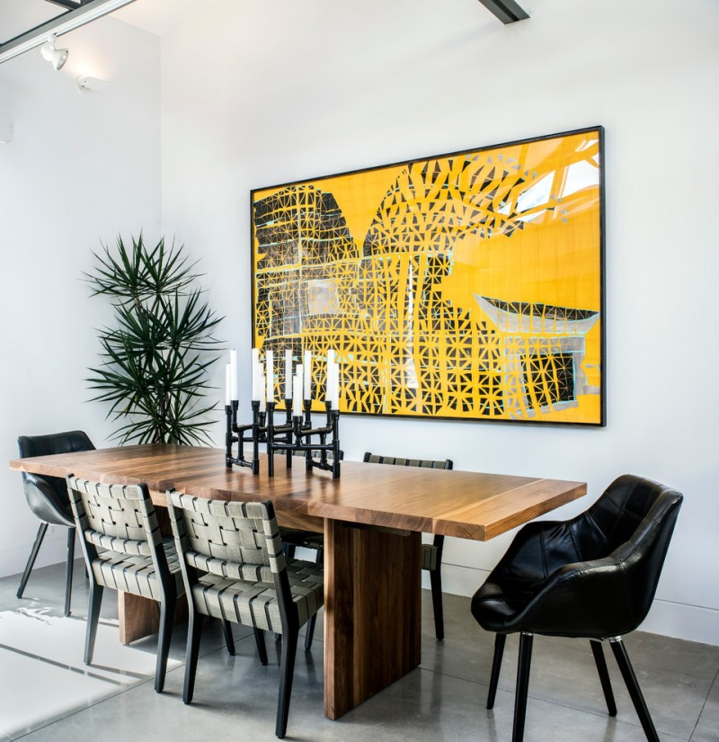 giant wall art yellow and black wall art white walls indoor plant wooden dining table black leathered armchairs candle holder chairs