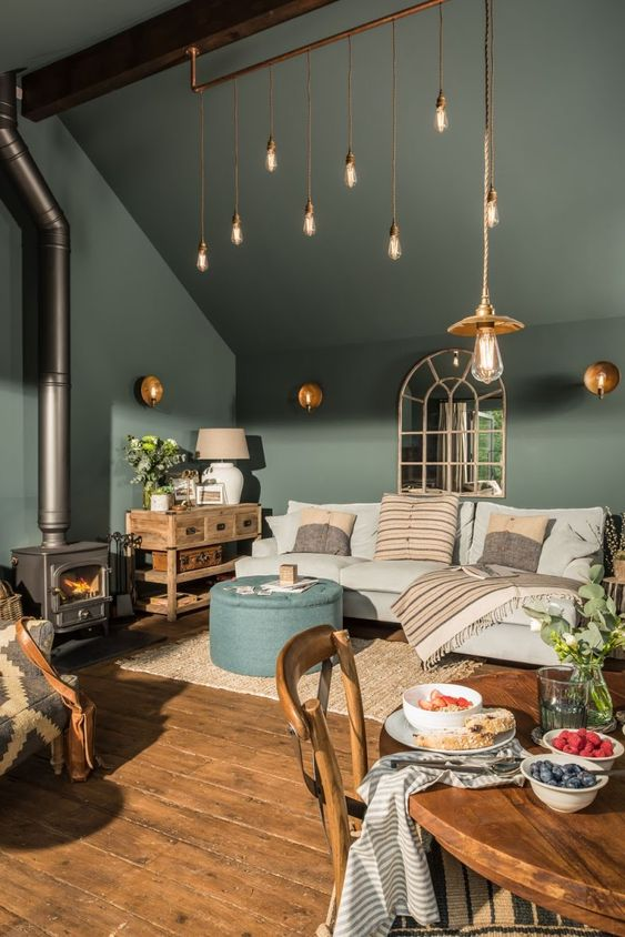 glass molten pendants on golden straight lines on the ceiling, wooden floor, blue round ottoman, grey sofa, wooden round dining table, wooden chairs, green wall ceiling
