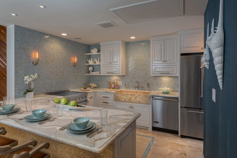 glass mosaic backsplash blue mosaic backsplash tile white cabinet barstools beige floor tile apron sink faucet stovetop refrigerator dishwasher white marble countertop