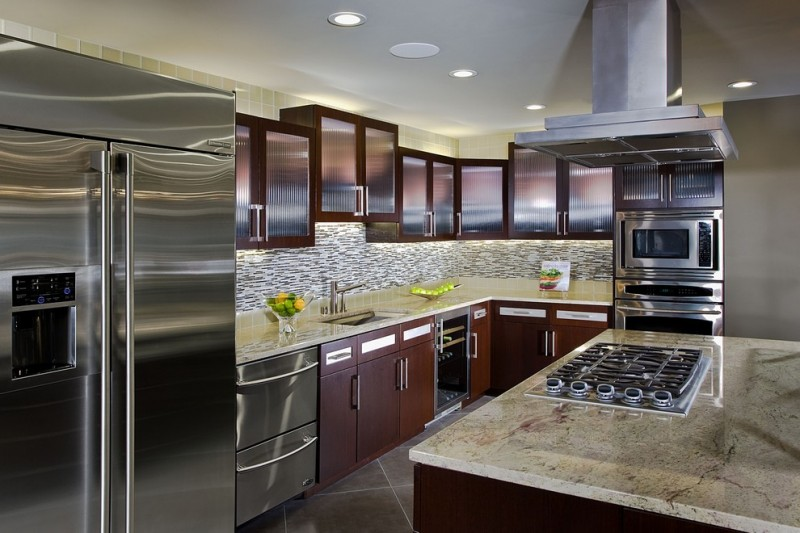 glass mosaic backsplash range hood brown cabinet frosted glass doors refrigerator granite countertop island dishwasher sink stovetop gray floor tile
