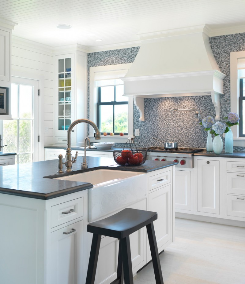 glass mosaic backsplash white cabinet white island white range hood stovetop white farmhouse sink faucet shelves glass door oven black barstools black countertops