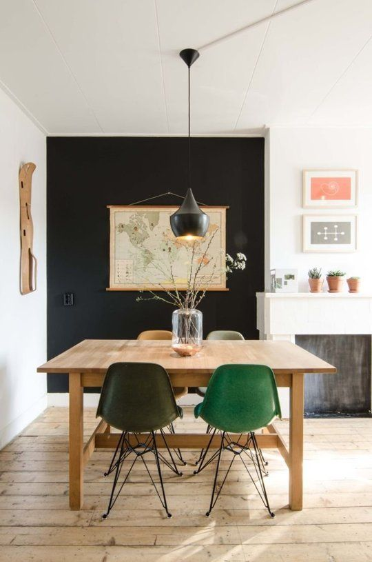 green yellows grey mid century modern chair, wooden table, wooden floor, black statement wall, black pendant