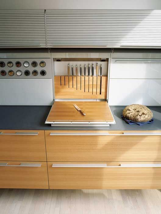 high end kitchen storage on the wall with vertical doors, grey kitchen top, wooden long drawers
