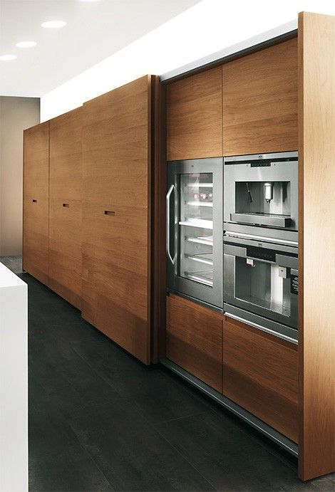 high end kitchen storage with wooden sliding door, pantry inside, dark grey floor, white wall, white sink