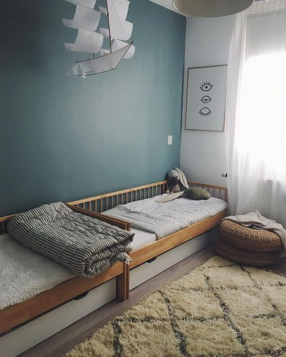 kids bedroom, white wall, green wall, wooden floor, rug, wooden bed platform, white drawer under, rattan ottoman