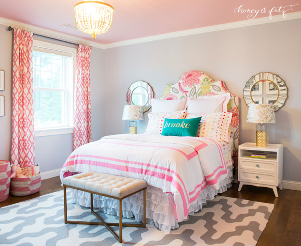 kids bedroom, wooden floor, pattern white rug, grey wall, pink ceiling, flower patterned headboard, white bed, white wooden side table, mirror, white bench, chandelier