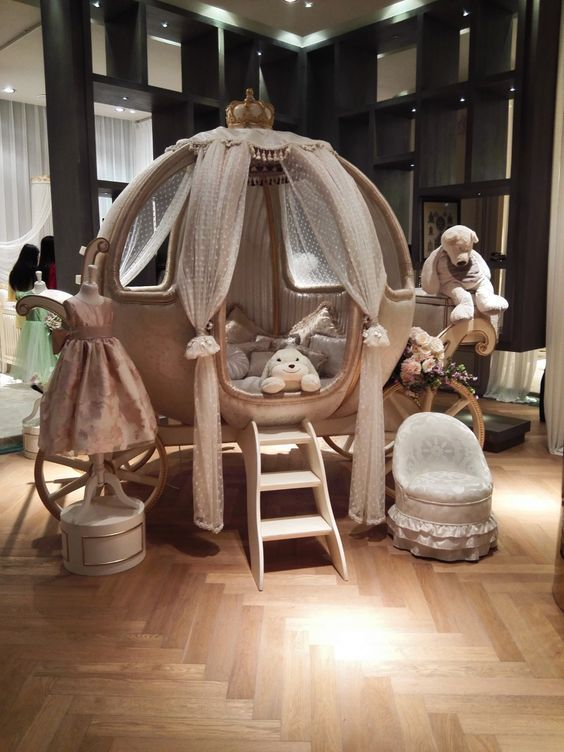 kids bedroom, wooden herringbone floor, carriage bed patform with round globe shape, windows and curtain on the carriage, white low chair