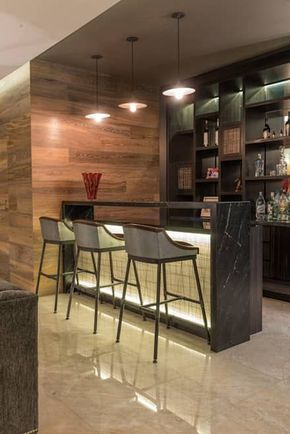 kitchen bar, marble floor, wooden wall, black marble bar with white tiles on its front, black shelves on the back, pendants, stools