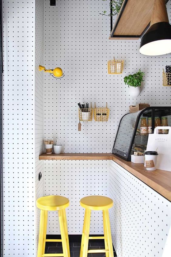 kitchen, black floor tiles, white pegboards on the wall and the surface of the island, yellow sconce, yellow stool, hanging shelves