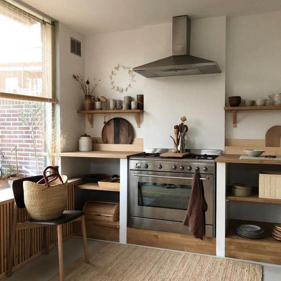 kitchen, grey floor, rattan rug, white wall, wooden botto sheles with wooden top, glass window, wooden floating shelves, silver hood